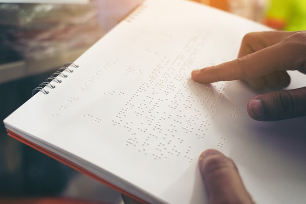 Конец-вверх пальцев читая брайль, рука слепого человека читая некоторый текст брайля книги брайля.