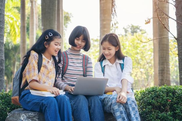 学生の若いアジア一緒に本を読んでタブレット、高校のキャンパスでラップトップコンピューター、夏休みのリラクゼーションの大学に笑みを浮かべて勉強します。