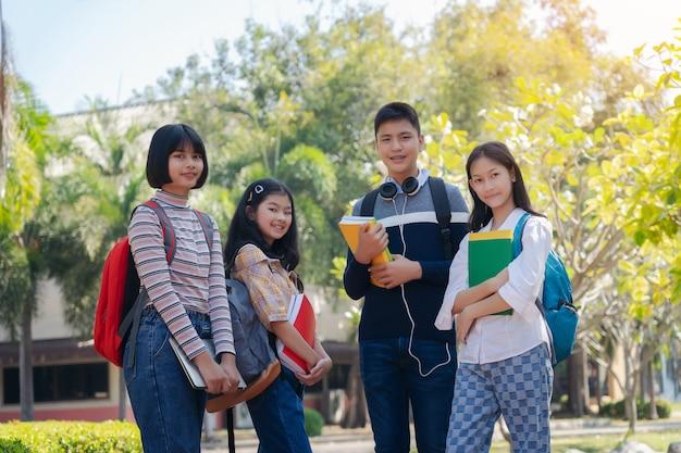 屋外、多様な若い学生本屋外コンセプトを歩いて学生幸せな若者のグループ