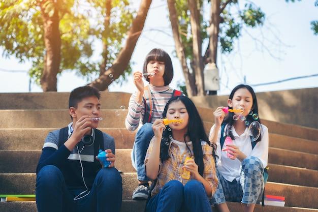 シャボン玉を吹くと屋外の夏の公園で楽しんでいる子供のグループ