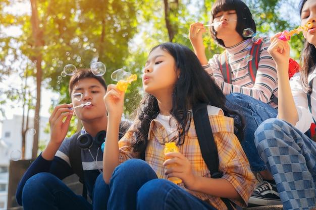 シャボン玉を吹くと夏の公園屋外で楽しんでいる子供のクローズアップ