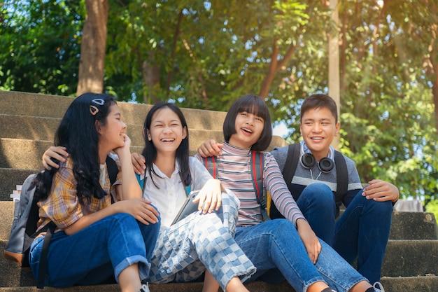 Группа студенческой молодежи и образование читает книгу в городском парке
