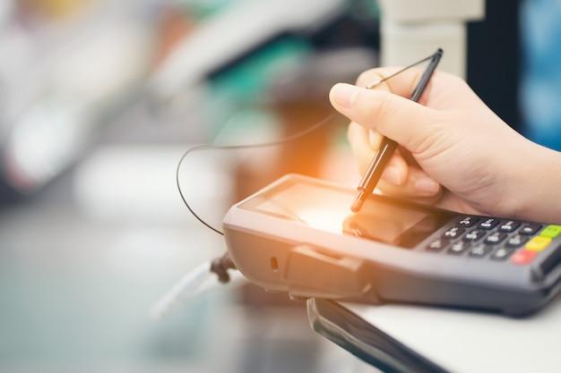 Крупный план подписи руки потребителя на сенсорном экране квитанции транзакции продажи кредитной карты