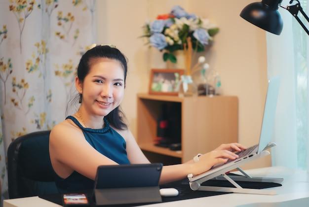 Женщина работает на ноутбуке в своем доме