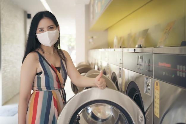 コインランドリーショップで洗濯をしてマスクを持つ美しい女性。