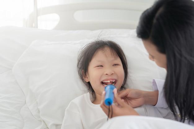 小児科医医師が少女を調べます。