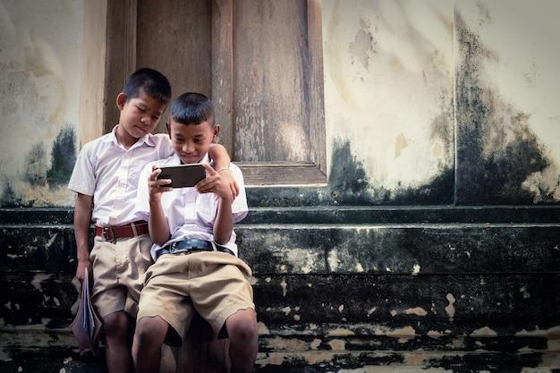 Два азиатских мальчика в школьной форме играют в игру