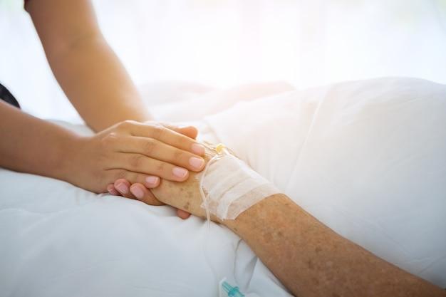 高齢者の患者の手を握って彼女を慰める医者