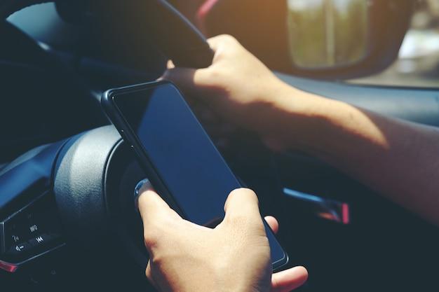 車の中にスマートフォンを持っている手の中のクローズアップインテリア、