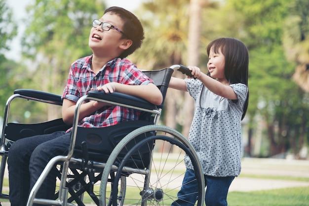 女の子と車いすでハッピーボーイは彼女の兄弟の笑顔の車椅子を運転しようとする