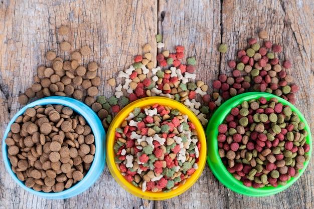 Сухой корм для собак и кошек в миске против деревянного фона