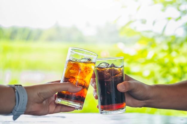 男性と女性の手は、コーラのガラスを与える。