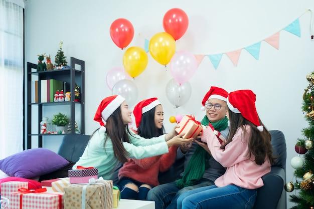 自宅でクリスマスを祝う友人のグループを示す画像。