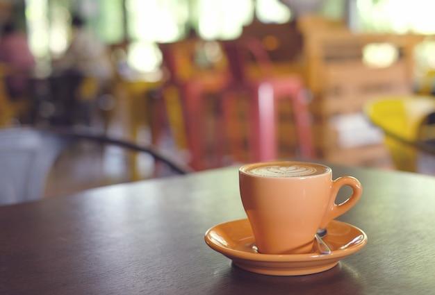 ぼやけて背景を持つホットコーヒー