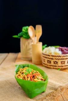 木製のフォークとスプーンで木製の机に置かれたバナナの葉の竹のスパイシーなサラダ