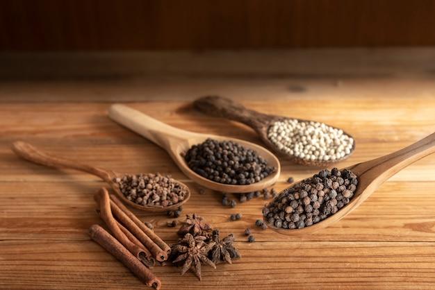木製のテーブルの上のスパイスパウダーで木のスプーンサラウンドで黒胡椒を閉じる
