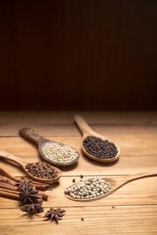 木製のテーブルの上のスパイスパウダーで木のスプーンサラウンドの白唐辛子を閉じる