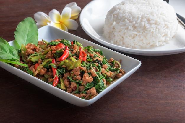 濃い茶色のテーブルの上の白い皿にバジルの葉と揚げ豚肉とご飯を閉じる