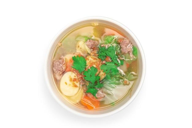 Свиные отбивные и суп из тофу на белой миске на белом фоне