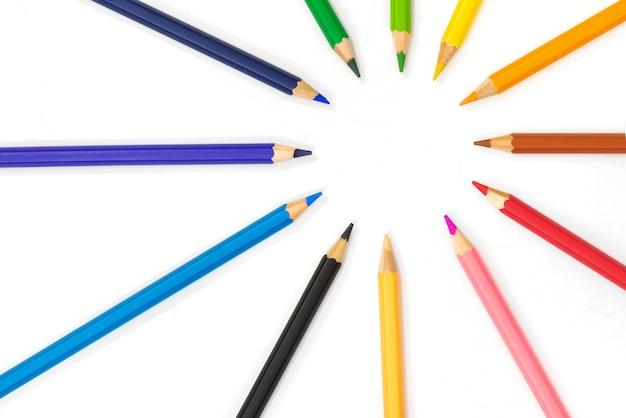 Цветные карандаши указывают вместе на белом фоне