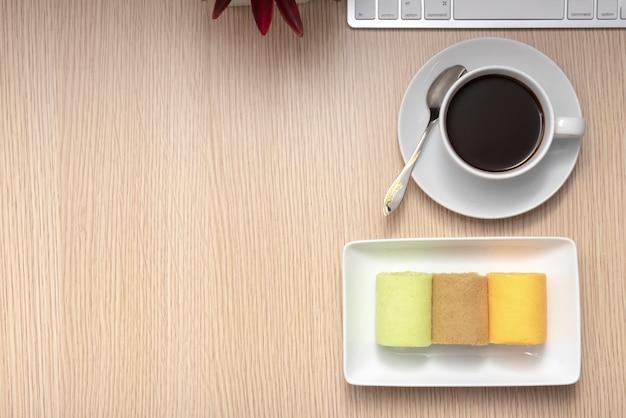 カラフルなロールケーキとパターンウッドの背景にコーヒー