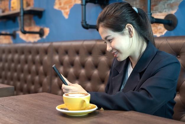 アジアの女性は、コーヒーショップで一杯のコーヒーとスマートフォンを保持します。