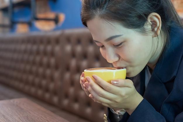 女性はコーヒーカップを保持し、コーヒーショップで飲む