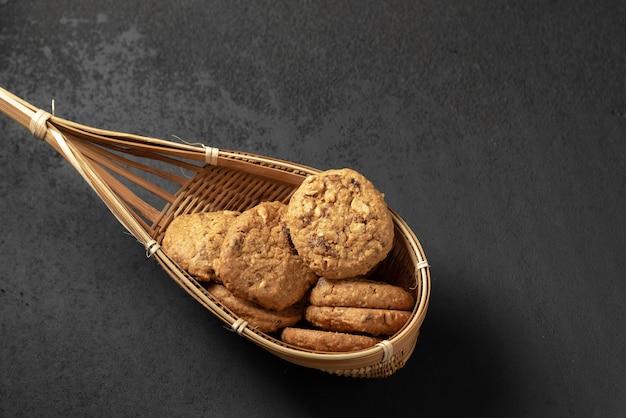 Печенье в бамбуковой корзине на черном фоне