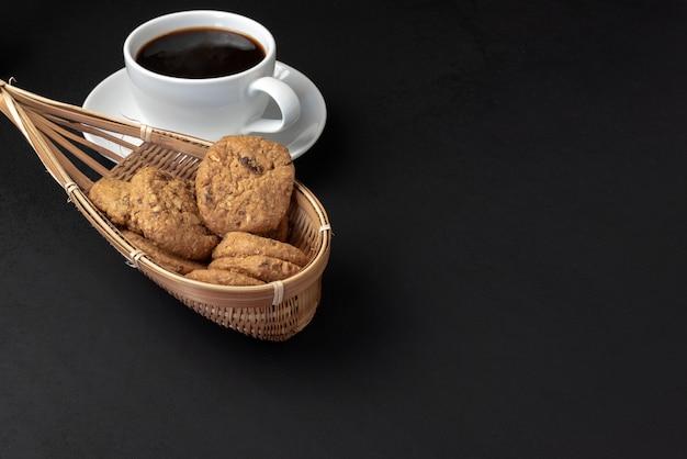Печенье в бамбуковой корзине и чашка кофе на черном фоне