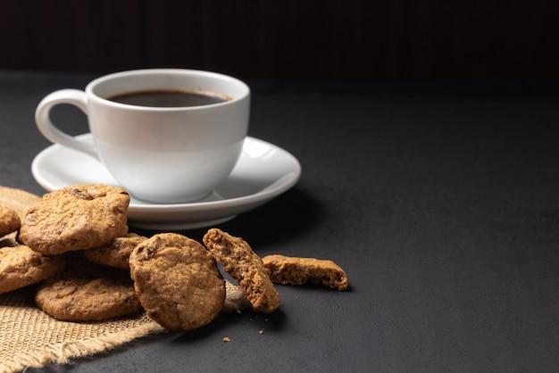 Печенье в бамбуковой японской циновке и чашка кофе на черном фоне