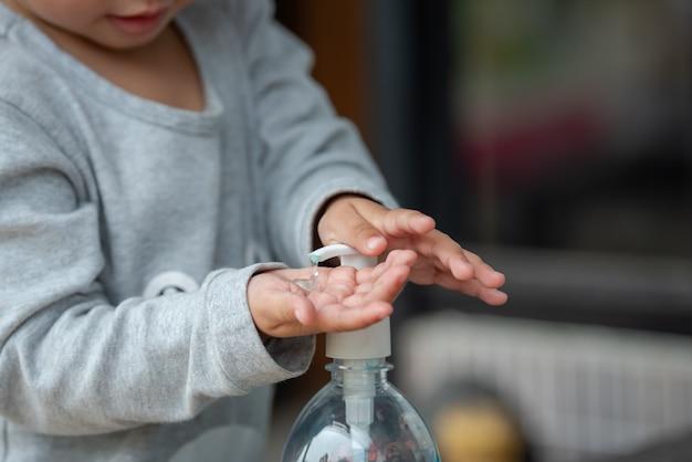 Ребенок, используя дезинфицирующее средство для рук.