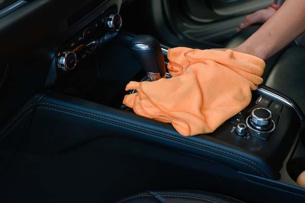 Рука с салфеткой из микрофибры для чистки салона автомобиля.