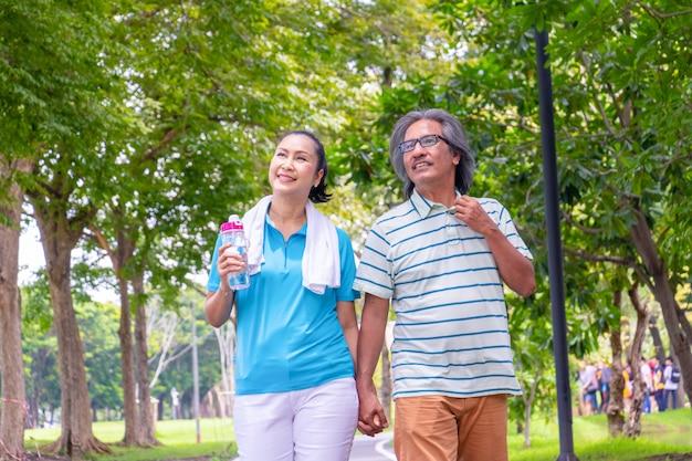 ジョギングの後、古いカップルがリラックスします。彼らは手をつないで笑う。