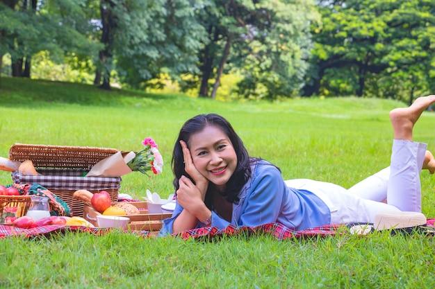 Молодая азиатская женщина ослабляет время в парке.