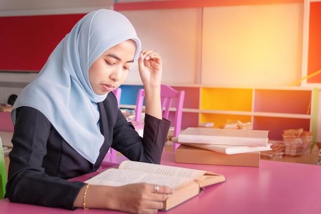 若い学生イスラムの女性。彼女は座って本を読んでいます。
