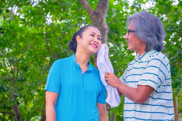 Они счастливая азиатская пара. человек тереть лицо женщины после пробежки в парке