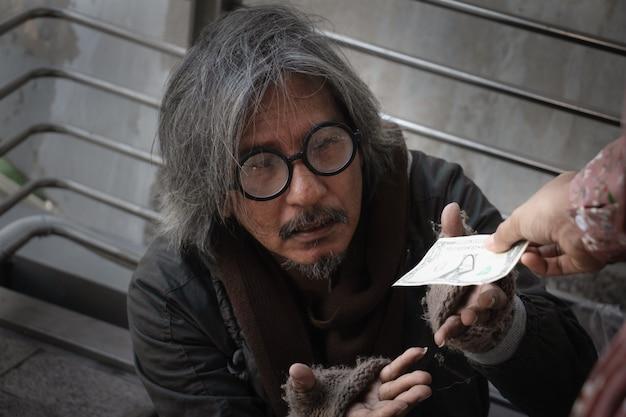 ホームレスの男性は町の歩道に座っています。彼は帽子をかぶってドルを受け取る。