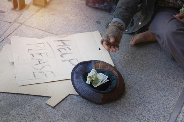 ホームレスの男性が町の歩道に座っています。彼は帽子でドルを受け取っています