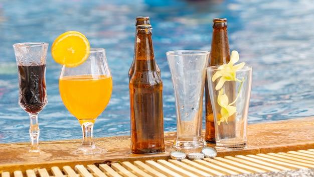 デッキでのエキゾチックなカクテルとビールのボトル