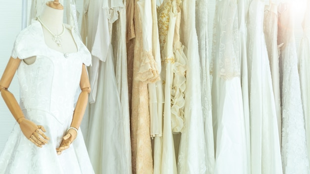結婚式のファッションは、掛かっている物干し用花嫁の白いドレスの背景を持つインテリアスタジオをドレスアップします。
