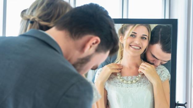 幸せな愛の気持ちで試着室で反射ガラスを探して宝石ネックレスを身に着けている新郎男と女の花嫁。