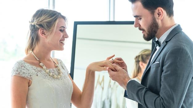 新郎は結婚式のファッションで彼の素敵な花嫁の指に指輪を置き、摩耗のスーツと花嫁のドレスでインテリアスタジオをドレスアップします。