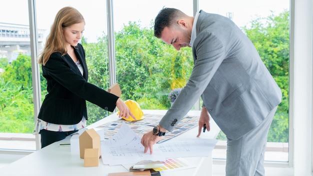 Бизнес-архитекторы представляют чертежную архитектуру с концептуальной моделью здания и материалом на столе.