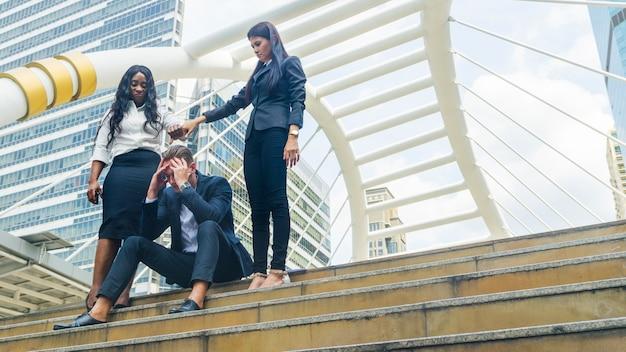 グループの女性の人々のビジネスは怒りを感じ、ビジネスを強調した男に手を差し伸べる
