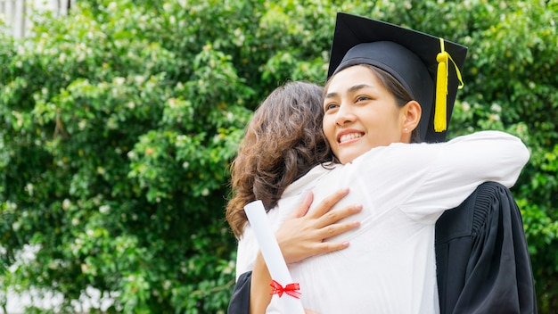 Студентка в выпускном платье и шляпе обнимает родителя на церемонии поздравления.