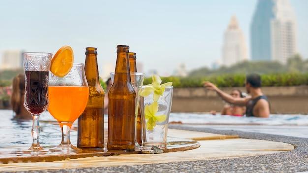 エキゾチックなカクテルとビールのボトル入りのドリンクとジュースドリンクをプールにセット