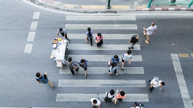 歩行者の歩行の道の上の眺めの横断歩道の向こう側の人々