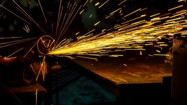 作業者は切断機を使って金属を切断する