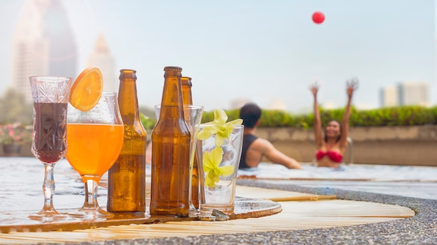 飲み物のカクテルや人々の背景とプールのビールのボトルパーティー