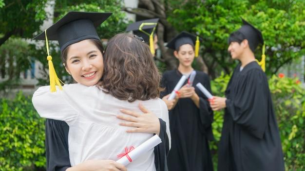 卒業式のガウンと帽子を持つ少女の学生は、お祝いの式典で親を抱きしめます。